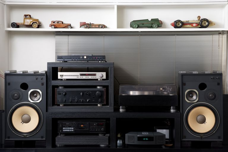 A Hi-Fi sound system underneath a shelf lined with vintage toy cars
