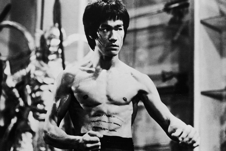 1973: American actor and martial artist Bruce Lee (1940 - 1973) poses in a fighting stance, with his arms by his waist, in a still from the film 'Enter The Dragon'. He has several scratches on his face.
