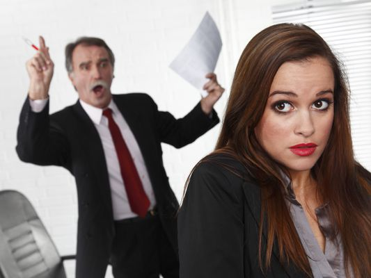 Man yelling at cringing woman in the office