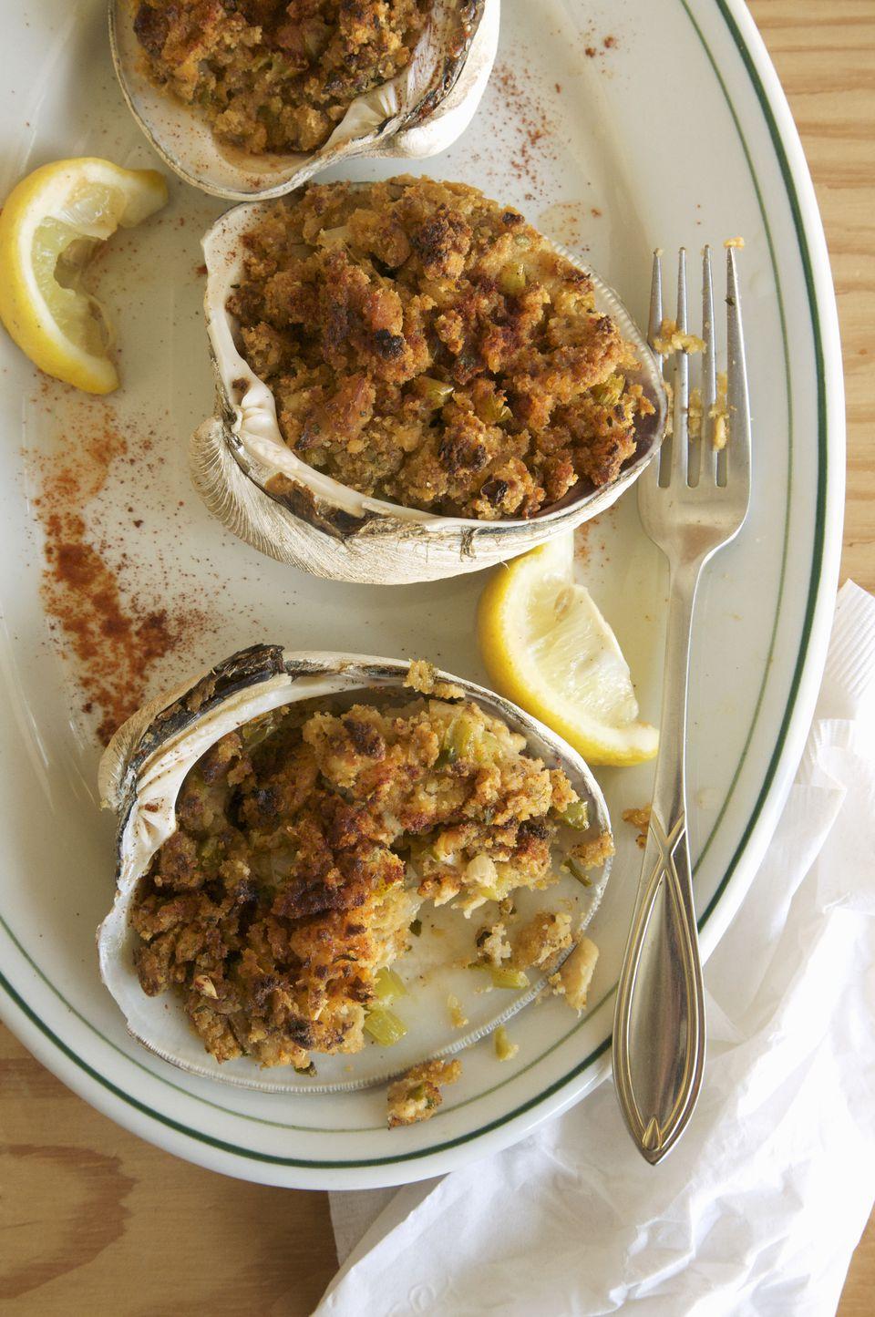 Stuffed clams with lemon garnish on plate, close up