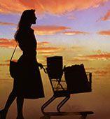 woman pushing shopping cart in the sunset