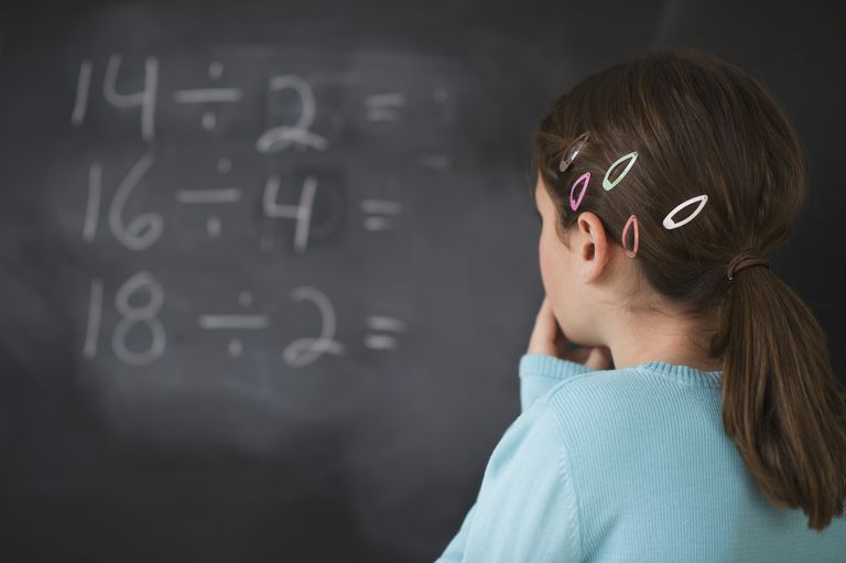 Girl looking at math equations on blackboard