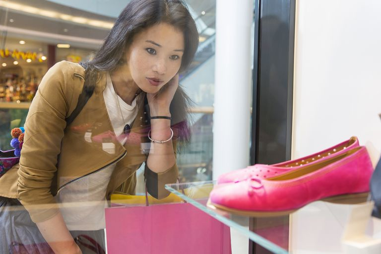 Young woman looking in shop window at a pair of pink flat shoes.