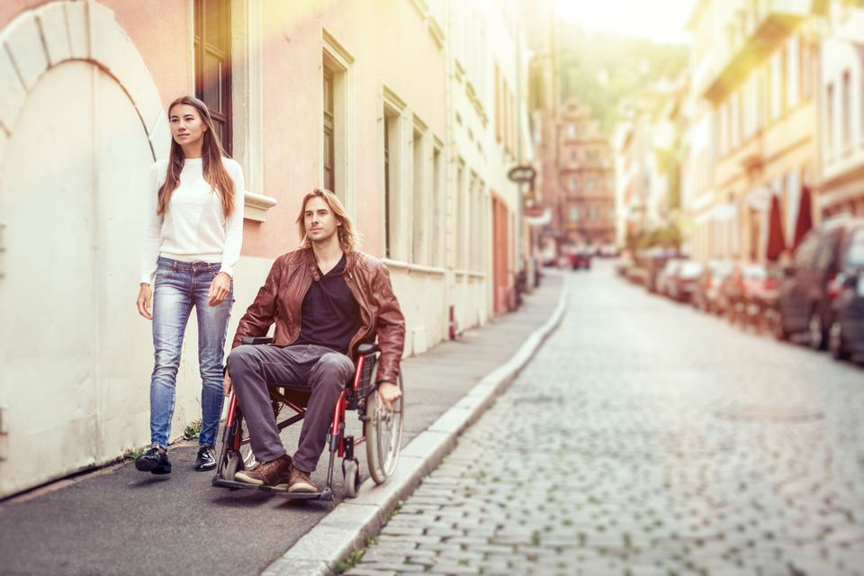 Young couple in wheelchair strolling in Heidelberg, Germany.