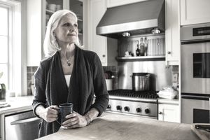 senior woman drinking coffee in kitchen
