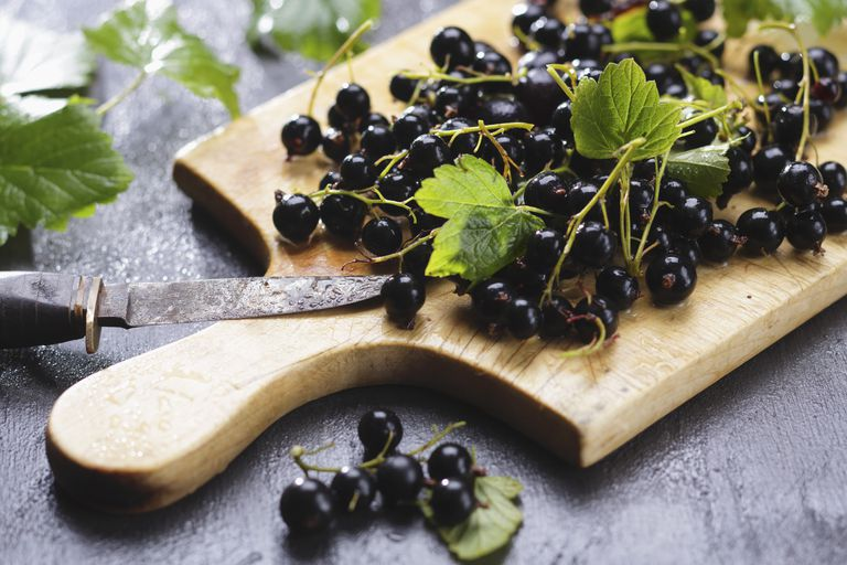 Black currants and leaves on a cutting board
