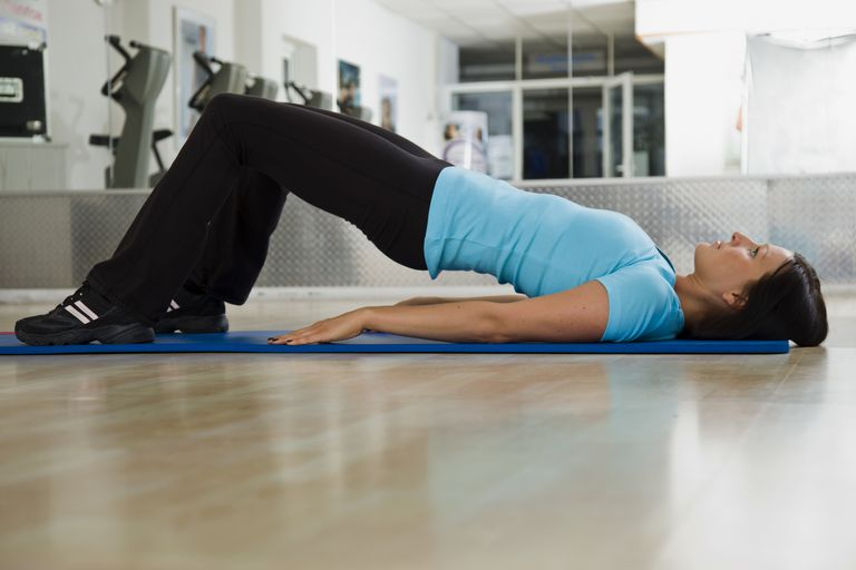woman doing glute bridge exercise on floor for warm up