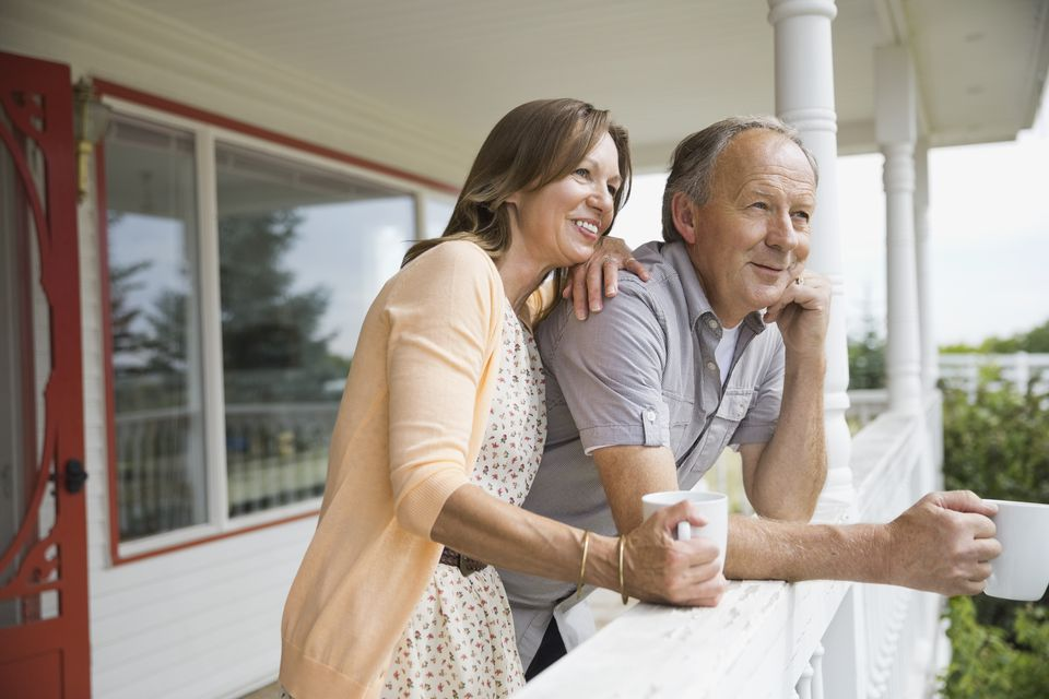 Senior couple drinking coffee on front porch