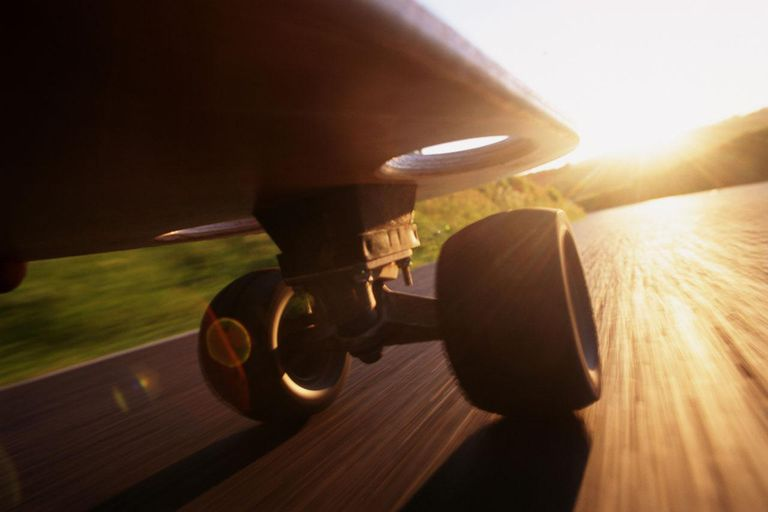 SKATEBOARD AT SUNSET, LOW ANGLE VIEW (BLURRED MOTION)