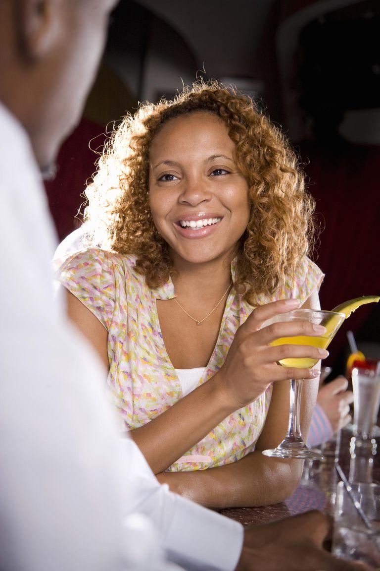Woman Drinking Cocktail at Bar Talking to Man