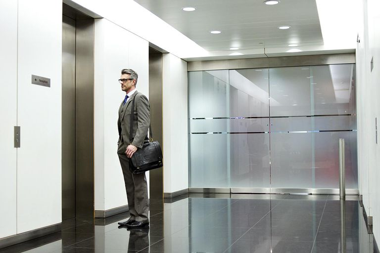 Businessman waiting for elevator in office corridor