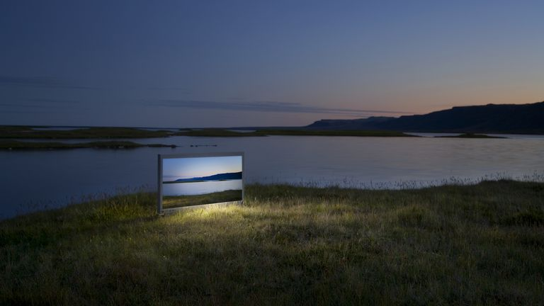 Wide screen television on landscape, showing exact picture of it, dusk