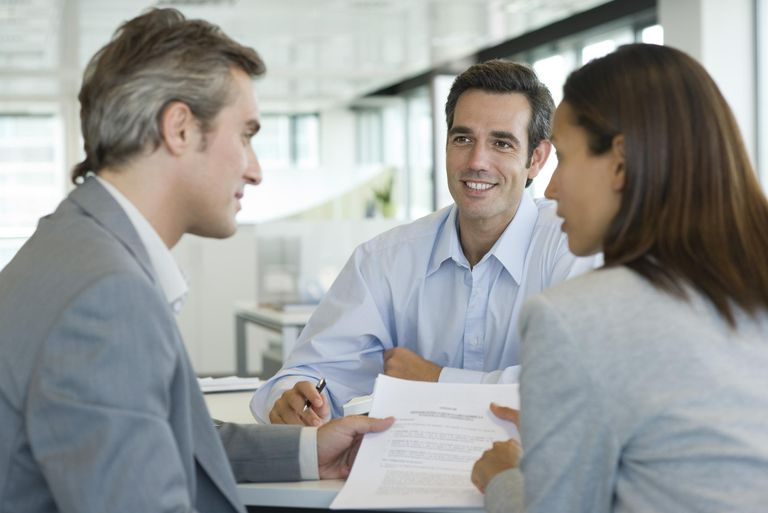 Couple discussing contract while meeting with businessman