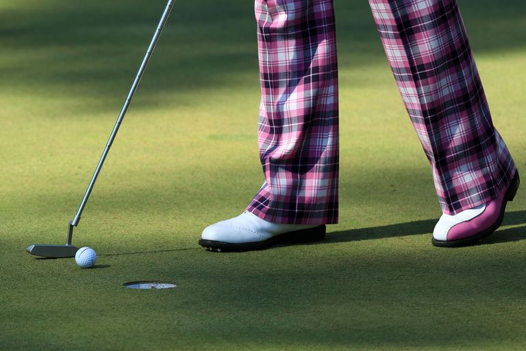 Golfer taps in a short putt