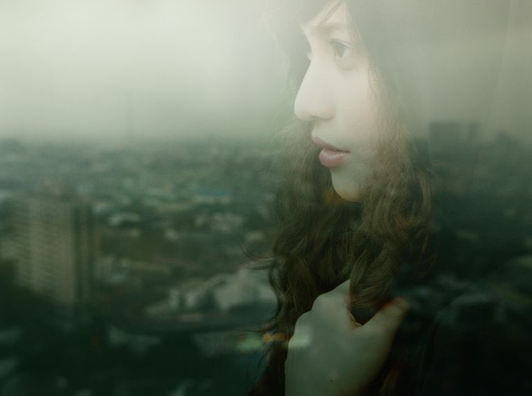 woman appearing distressed with blurry view of city in background