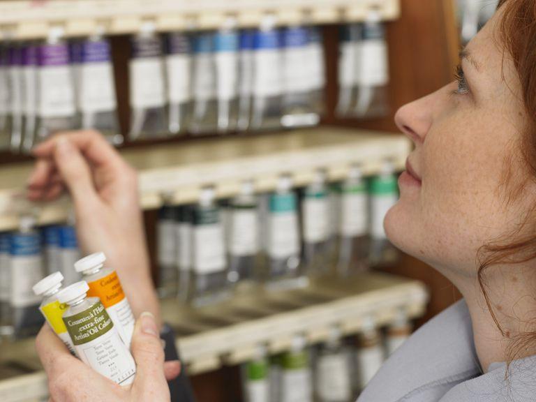 Mujer que selecciona los tubos de pintura en la tienda de arte perfil