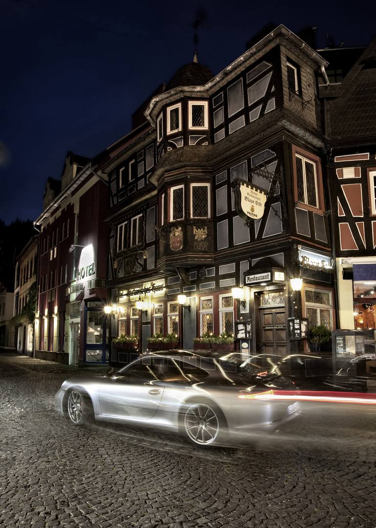 Porsche 911 driving in a German village street at night
