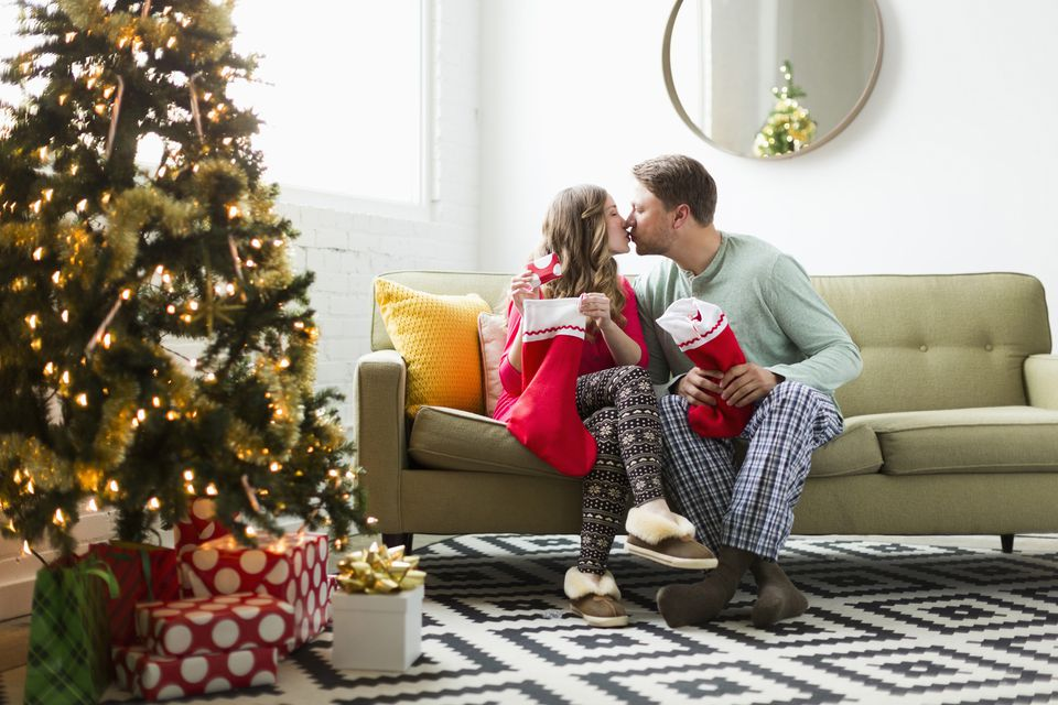 Young couple with Christmas stockings kissing on sofa
