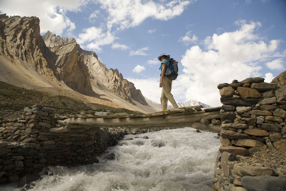 Woman crosses creek on small bridge during trek in Zanskar province, northern India.