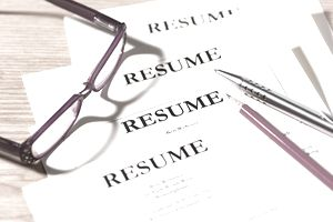 Pile of resumes with glasses and pen.