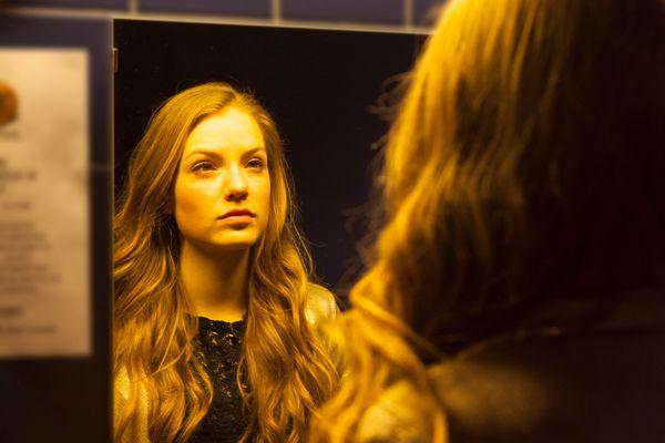 teen girl looking in mirror