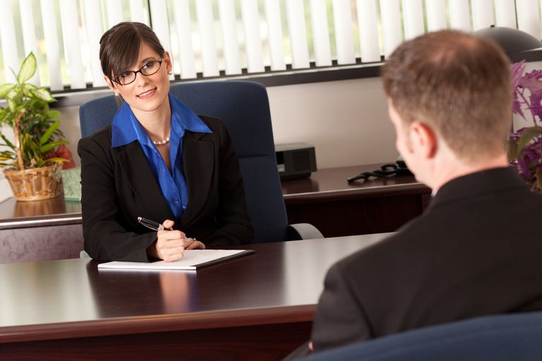 Young Businesswoman Interviewing Businessman at Desk in Office