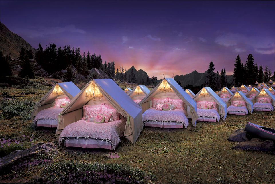 Glamping tents in a field at dusk