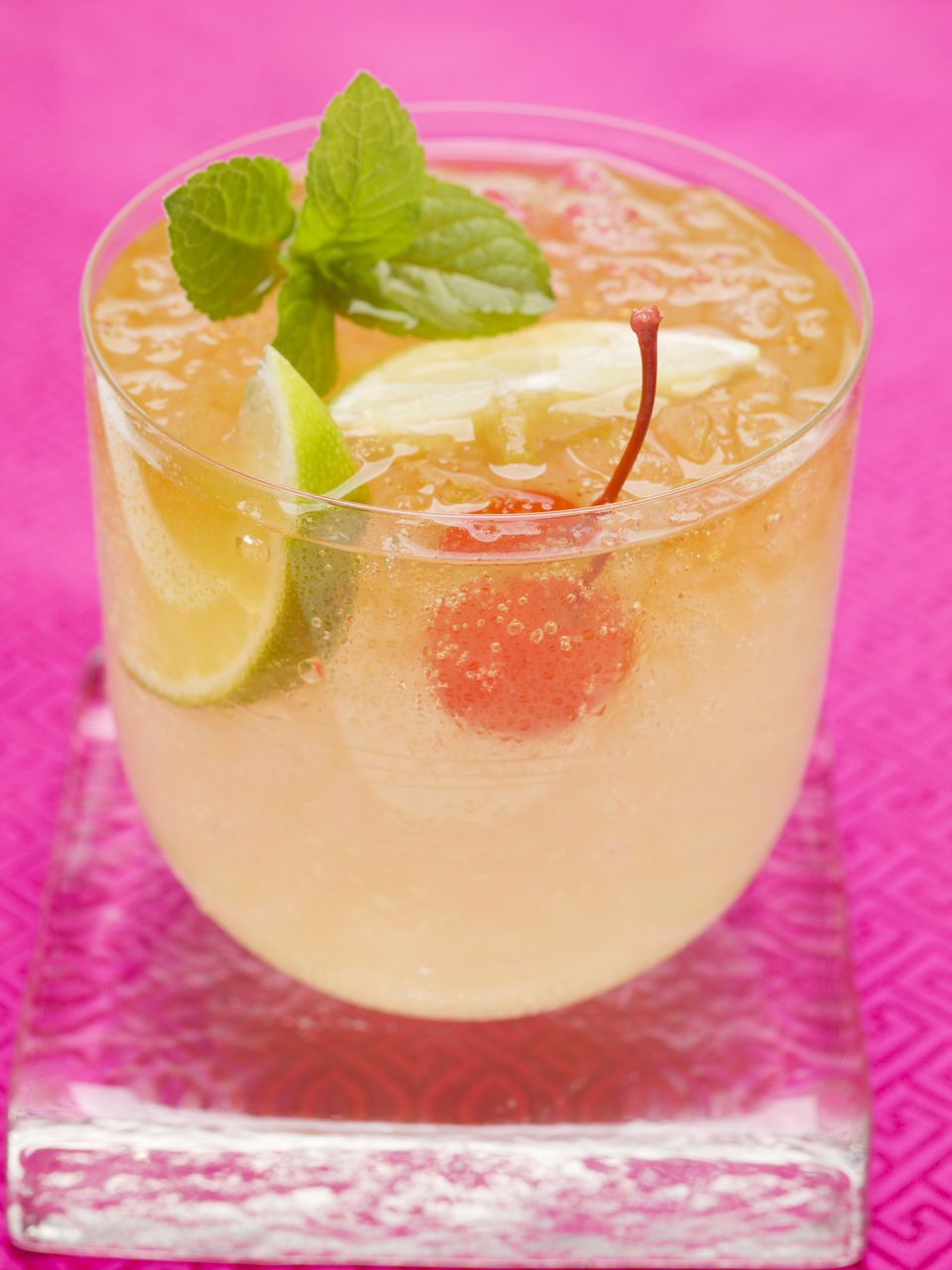 Classic Apricot Sour Cocktail with a Cherry, Lime, and Mint