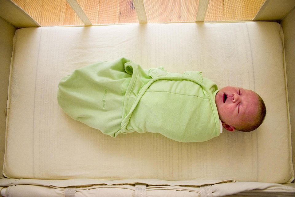 A one week old swaddled baby lies sleeping in a basinet.