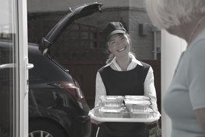 A volunteer delivering meals to the elderly.