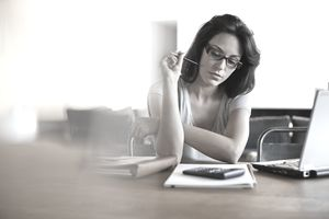 Woman sitting at a desk looking at a notebook