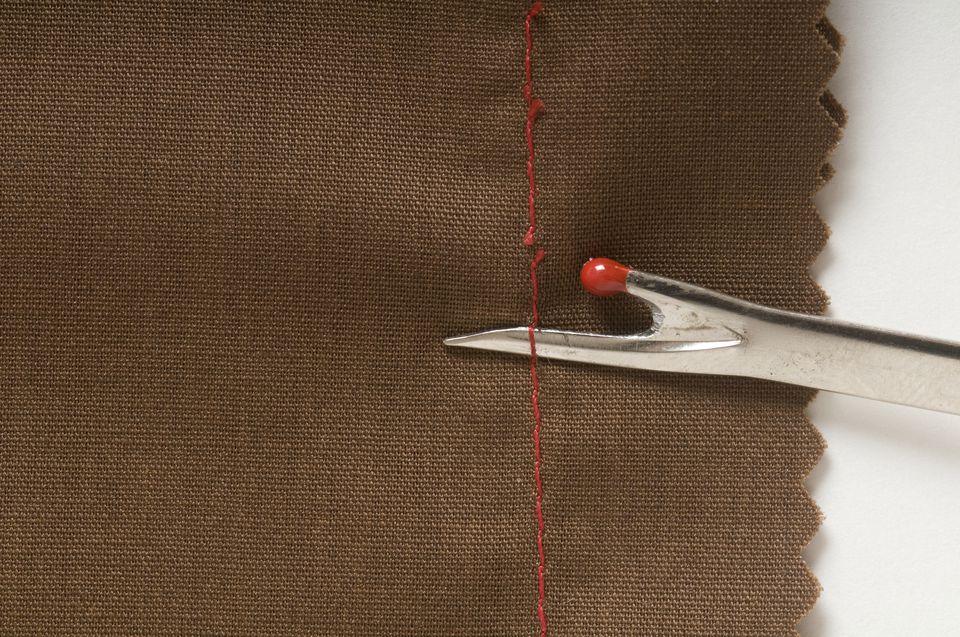 Unpicking stitches with a seam ripper, close-up