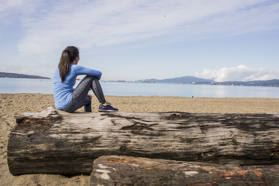 Young woman sitting on log, looking at view, English bay, Vancouver, Canada