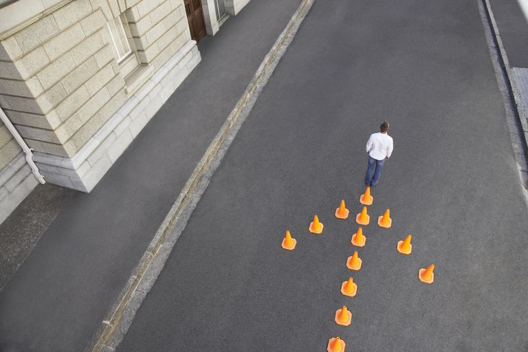Man standing in front of traffic cones in arrow-shape