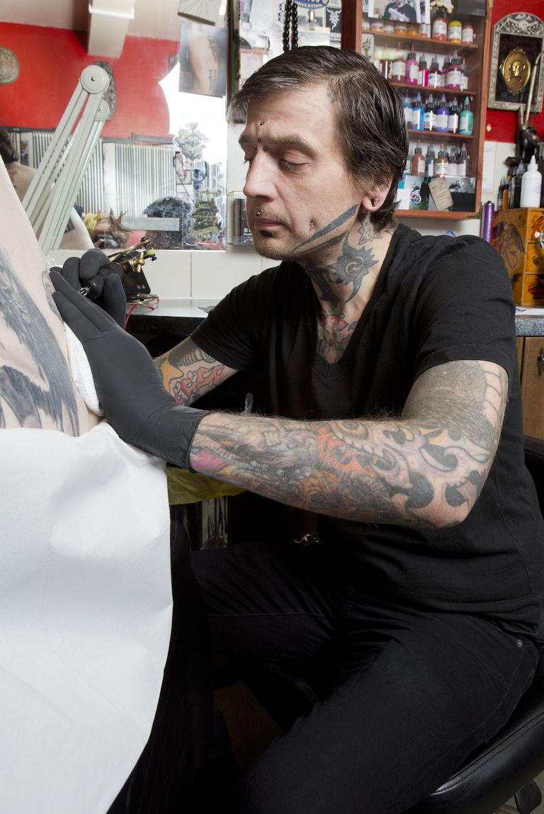 Tattoo artist doing a tattoo