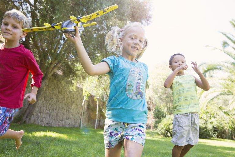3 kids play outside with toy airplane