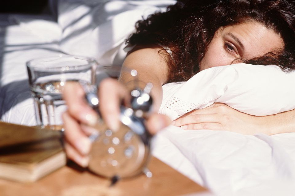 Woman lying in bed, turning off alarm clock