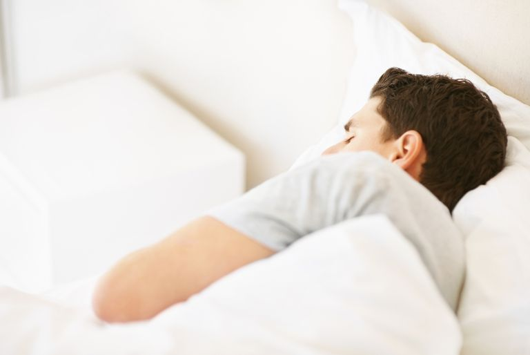 Young guy sleeping in bed