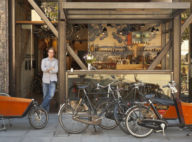 Man standing in doorway of bicycle shop