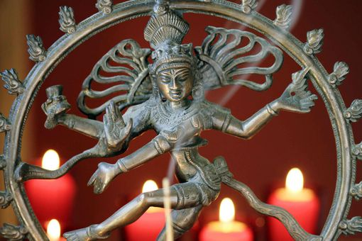 Hindu Shiva statue with candles and incense