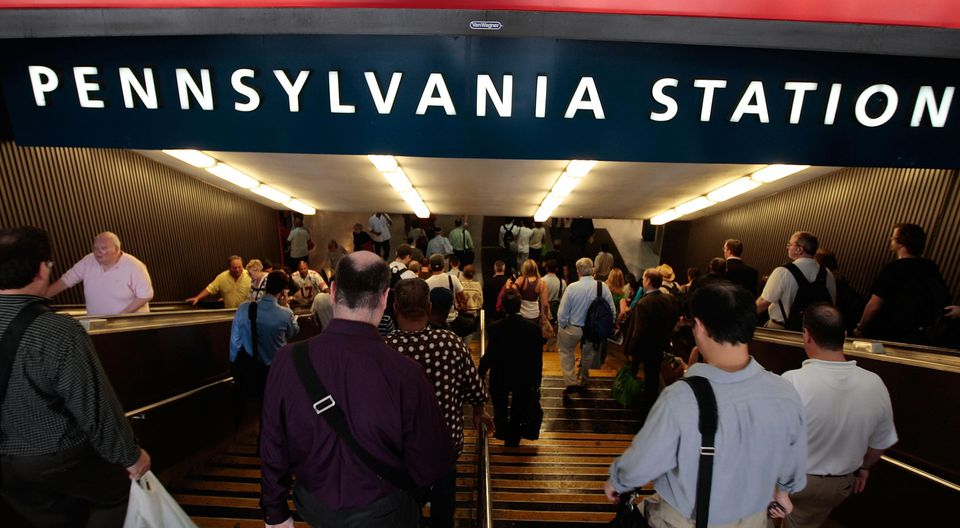 Travelers and commuters head down into Manhattan's Penn Station July 2, 2009 in New York City.