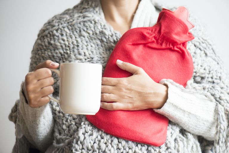 Woman holding cup of tea and hot water bottle
