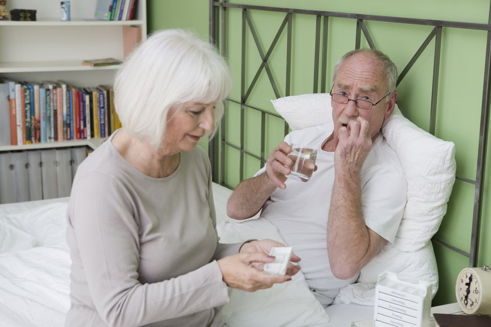 Senior woman caring for sick husband in bed
