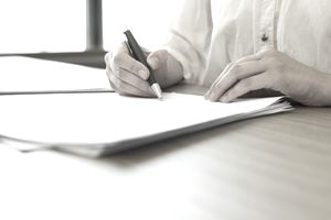 Man writing on paper with pen