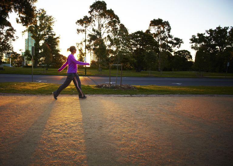 Woman walking on track at sunrise