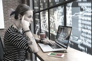 Business financial and forex concept, Hipster young Woman freelancer thinking about her job and using computer laptop showing trading graph with the stock exchange trading graph screen background