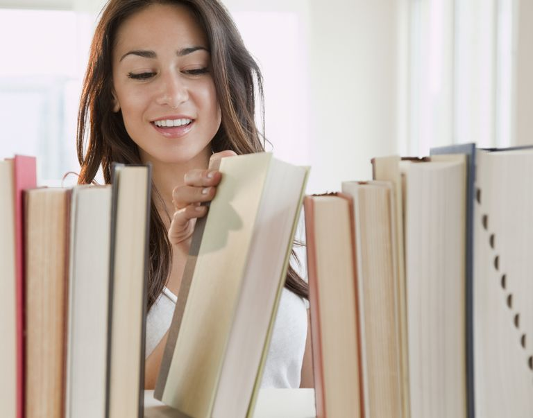 Hispanic woman removing book from shelf