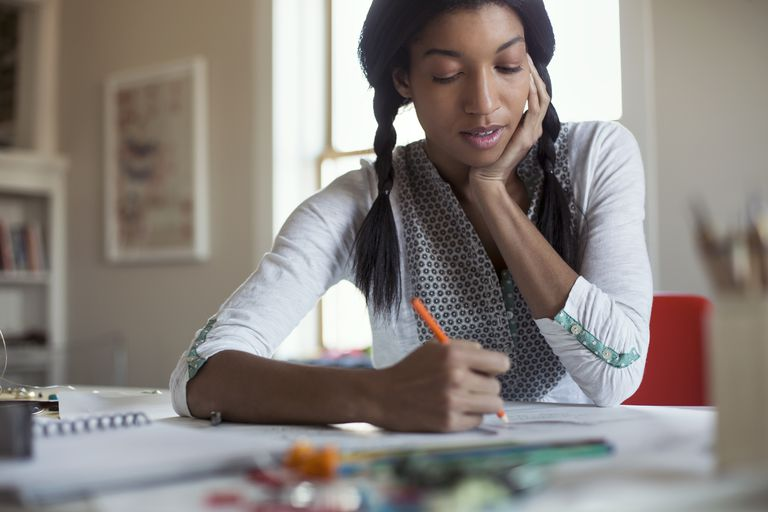 Mid adult female jewelry artist drawing at desk