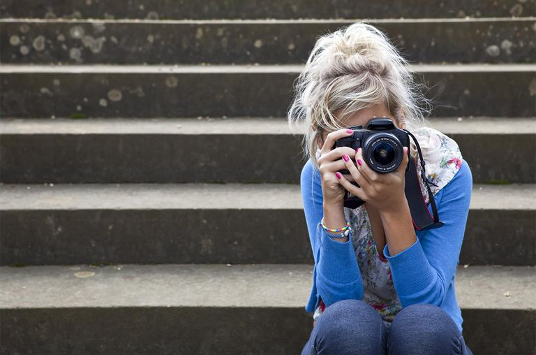 Blonde girl taking photographs while sitting on a flight of old stone steps.