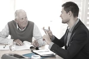 A lawyer speaking with an elderly man.